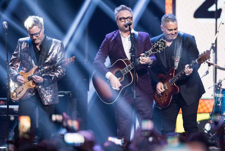 Kevin Hearn, left, and Ed Robertson, right, of the Barenaked Ladies, and former member and co-founder Steven Page, centre, perform during the 2018 Juno Awards in Vancouver, B.C.