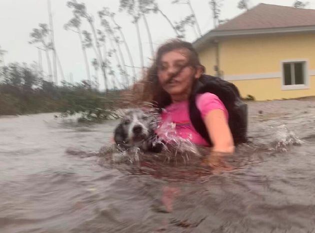 Julia Aylen wades through waist deep water carrying her pet dog as she is rescued from her flooded home...