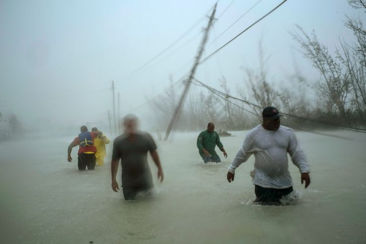 Volunteers walk under the wind and rain from Hurricane Dorian through a flooded road as they work to rescue families near the