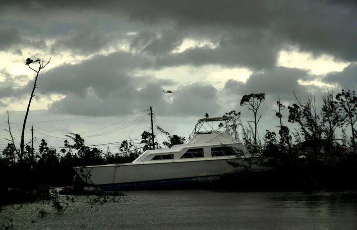 A United States Coast Guard helicopter flies over the areas affected by Hurricane Dorian, as a catamaran thrown onshore by th