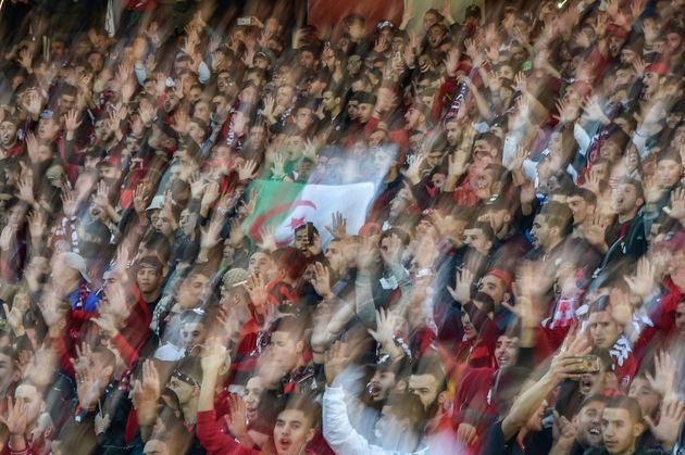 TOPSHOT - USM football club supporters cheer with an Algerian flag during the match against MC at the...