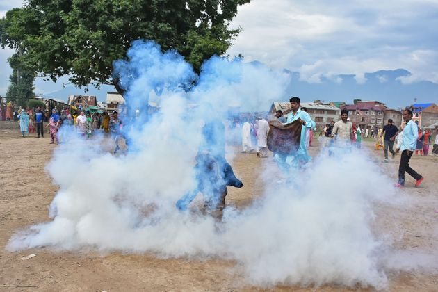 Kashmiri men try to block the teargas smoke during clashes between Indian forces and people in Srinagar...