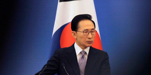 South Korea's President Lee Myung-bak stands in front of a South Korean national flag as he attends a...