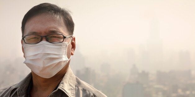 Asian man wearing mouth mask against air