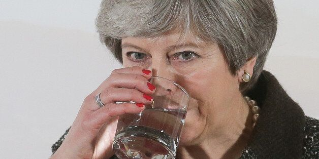 Britain's Prime Minister Theresa May drinks from her glass of water as she gives a speech on the environment...