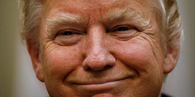 U.S. President Donald Trump smiles during a meeting with police and firefighters, who responded to the...