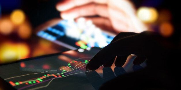 Silhouette finger on tablet with graph stock market trading screen with abstract blur smartphone bokeh...