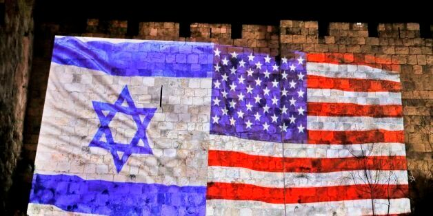 A picture taken on December 6, 2017 shows a giant US flag screened alongside Israel's national flag by...