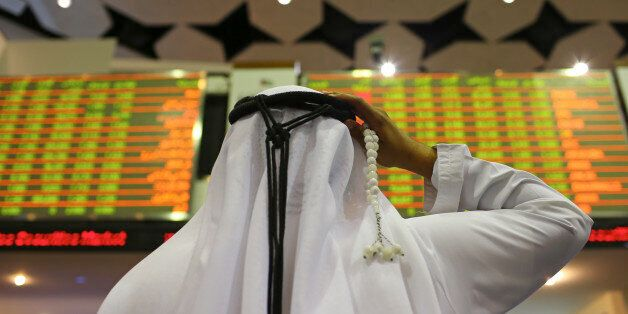 A visitor holds prayer beads while looking at financial information screens at the Dubai Financial Market...