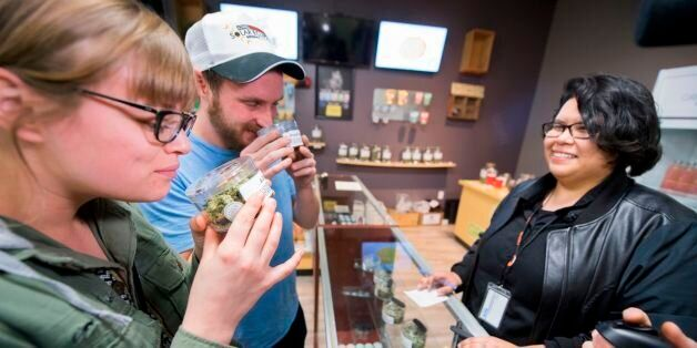Tourists Laura Torgerson and Ryan Sheehan, visiting from Arizona, smell cannabis buds at the Green Pearl...