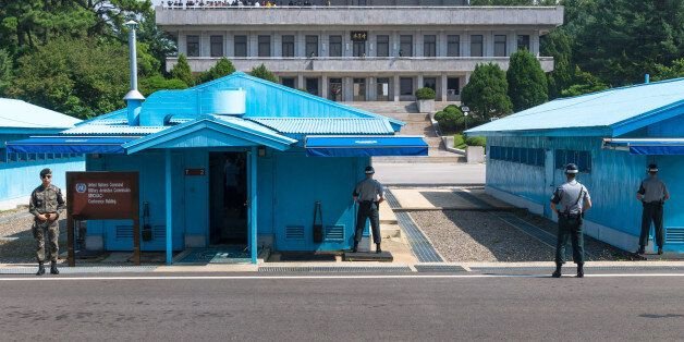 Jsa Within Dmz: UN soldiers close in front of blue buildings at North South Korean border with North...