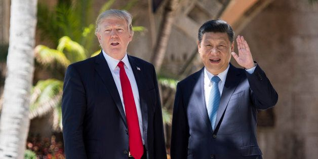 TOPSHOT - Chinese President Xi Jinping (R) waves to the press as he walks with US President Donald Trump...