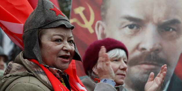 Demonstrators react in front of a portrait of Soviet state founder Vladimir Lenin during a rally held...