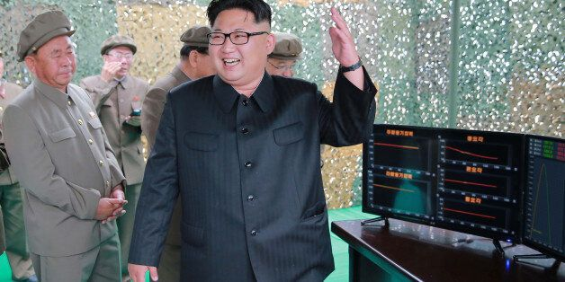 North Korean leader Kim Jong Un reacts during a test launch of ground-to-ground medium long-range ballistic...