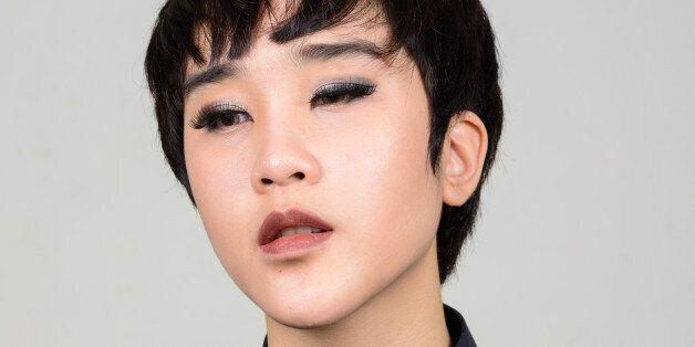 Studio shot of young Asian transgender teenage boy against gray background horizontal