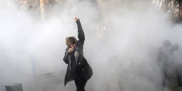 TOPSHOT - An Iranian woman raises her fist amid the smoke of tear gas at the University of Tehran during...