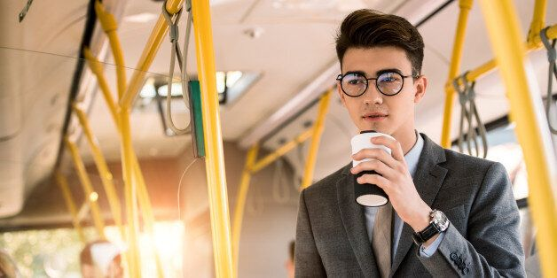 pensive young businessman in eyeglasses drinking coffee to go in