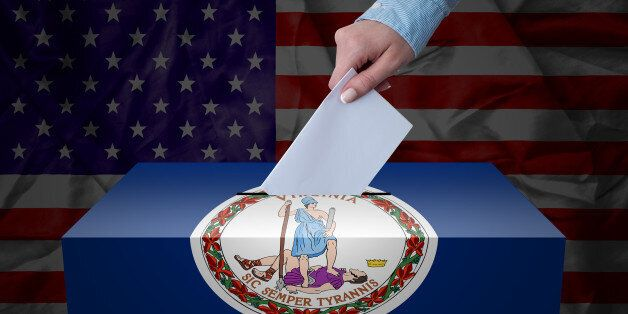 A hand casting a vote in a ballot box for an election in the Virginia,