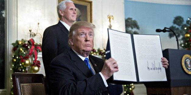 U.S. President Donald Trump holds up a proclamation next to U.S. Vice President Mike Pence, left, after...