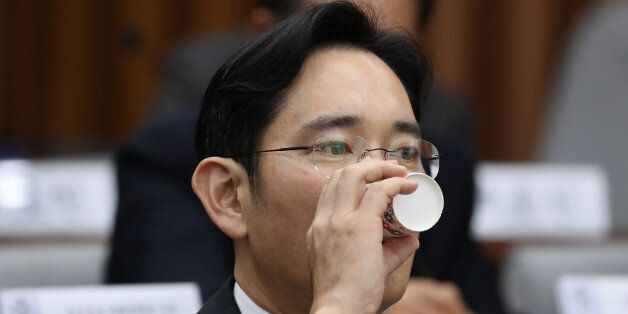 Jay Y. Lee, co-vice chairman of Samsung Electronics Co., takes a drink during a parliamentary hearing...