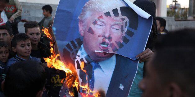 Palestinians burn posters of Israeli Prime Minister Benjamin Netanyahu and U.S. President Donald Trump,...