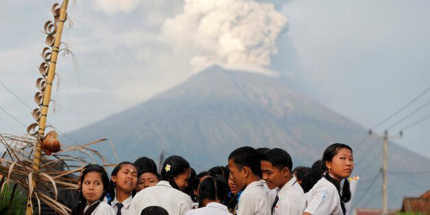 School children ride on the back of a truck on their way to school as Mount Agung volcano erupts in the...