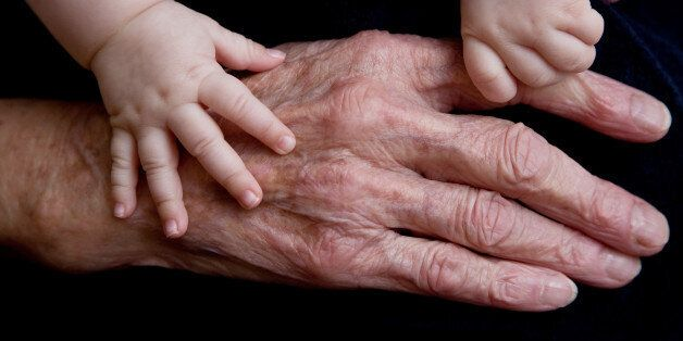 close up of a grand-grandmothers hand and small hands of 4 month old