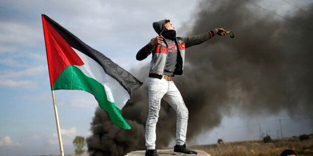 A Palestinian demonstrator uses a slingshot to hurl stones towards Israeli troops during clashes at a...