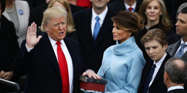 U.S. President-elect Donald Trump takes the oath of office as First Lady-elect Melania Trump stands during...