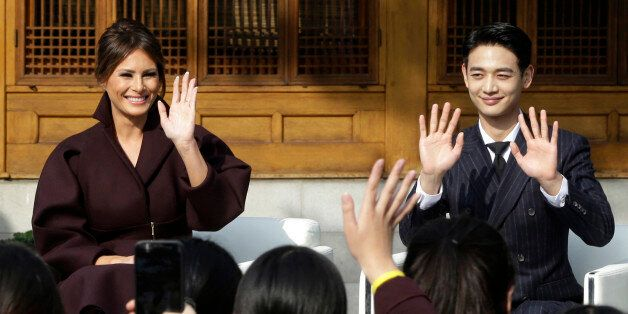 US First Lady Melania Trump (L) and Choi Min-ho, a member of South Korean boy band Shinee, wave to South...