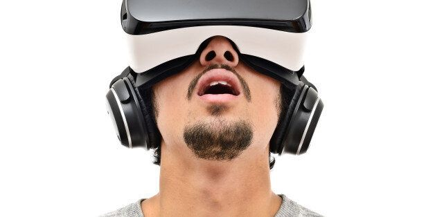 Young man wearing vr headset and handphones. Isolated on white. Wearable technology
