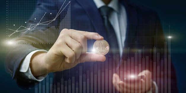 Bitcoin in the hands of a businessman on the background of the chart profit