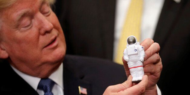 U.S. President Donald Trump holds a space astronaut toy as he participates in a signing ceremony for...