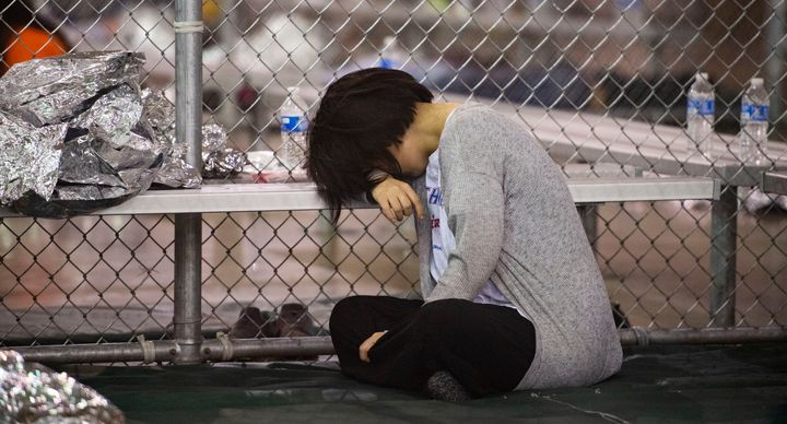A female minor rests her head on a bench in the US Border Patrol Central Processing Center in McAllen, Texas on August 12, 20