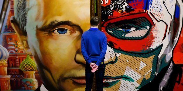 TOPSHOT - A man looks at a painting depicting Russian president Vladimir Putin at the 'SUPERPUTIN' exhibition...