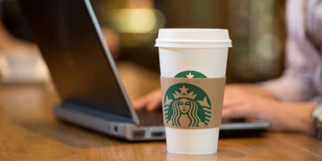 The Starbucks Corp. logo sits on a carboard coffee cup as a customer uses a laptop computer inside a...