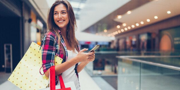 Happy girl with shopping bags texting on