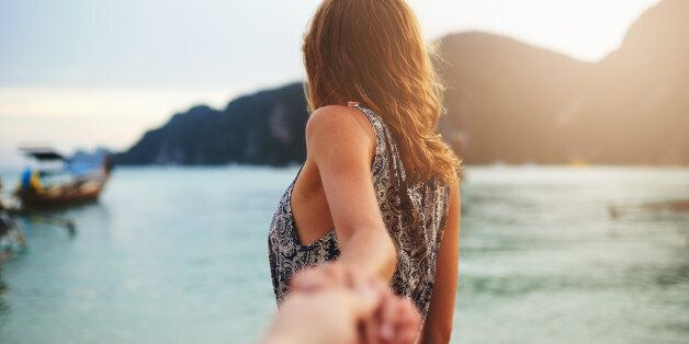 Shot of a young woman leading someone by the hand at the