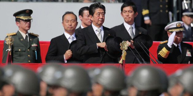 Japanese Prime Minister Shinzo Abe (C) reviews soldiers of the Ground Self-Defense Force during a military...