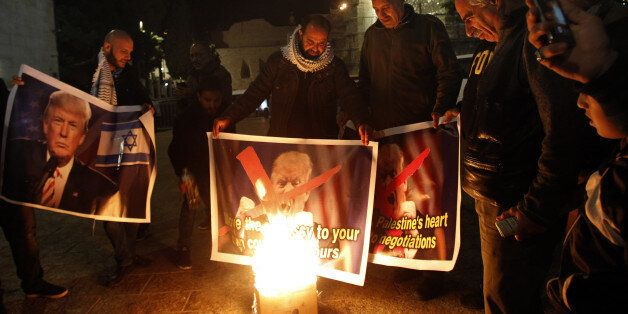 Palestinian protesters burn pictures of US President Donald Trump at the manger square in Bethlehem on...