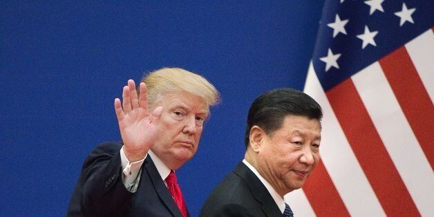US President Donald Trump (L) and China's President Xi Jinping leave a business leaders event at the...
