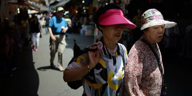 Elderly women wearing sun visors walk in a market in Seoul on May 30, 2014. Sun visors are a familiar...