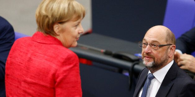 German Chancellor Angela Merkel speaks with Social Democratic Party (SPD) leader Martin Schulz as they...