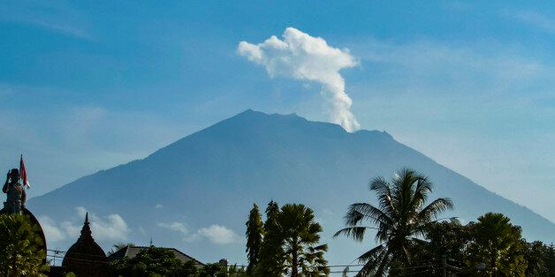 Mount Agung volcano spews steam and smoke into the air as seen from Bangli on Indonesia's resort island...