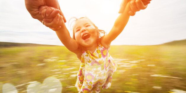 Happy girl spinning around her father in a field. Motion