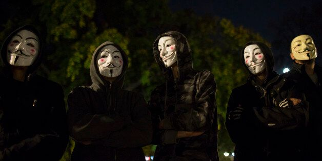 Protesters wearing Guy Fawkes masks stand in a park in downtown Belgrade November 5, 2014, on the day...