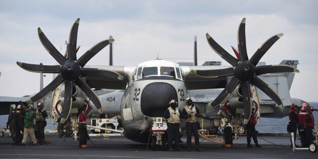 US Navy crew members stand by a C-2 Greyhound on the deck of the Nimitz-class aircraft carrier USS Carl...