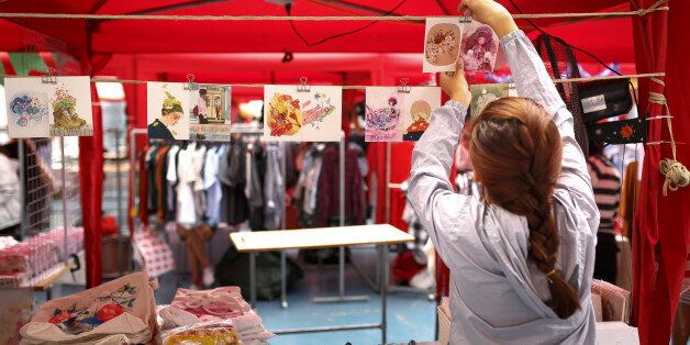 Ho Chi Minh city, Viet Nam - December 10, 2016: A young girl is hanging handmade postcards in the souvenir...