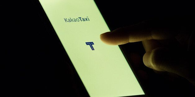 The KakaoTaxi application, developed by Daum Kakao Corp., is displayed on the screen of a mobile device...