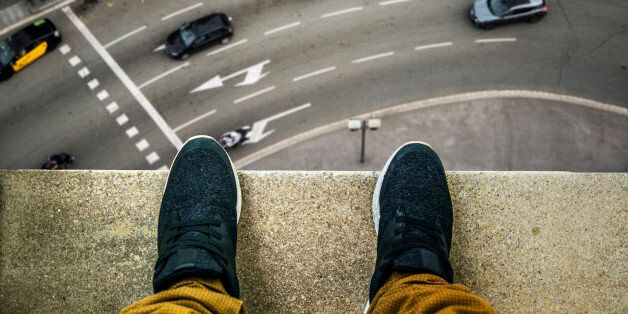 Two feet at the edge of a rooftop of a high building. A busy street appears looking